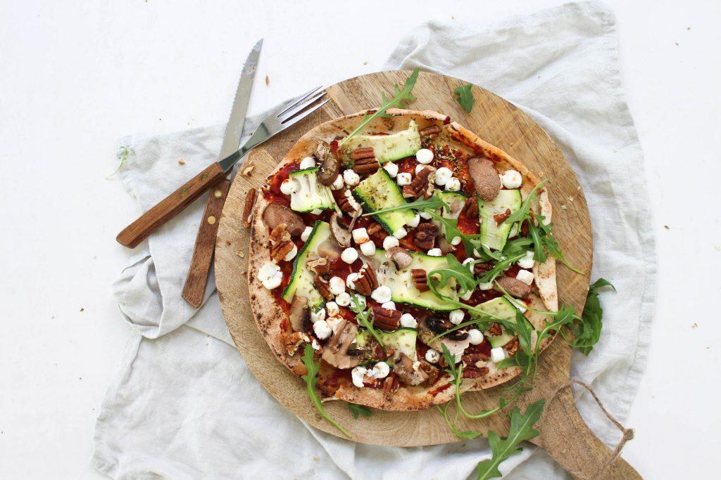 Pizza van Libanees platbrood met geitenkaas, courgette, walnoten en rucola
